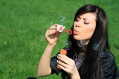 Woman blowing bubbles Stock Image