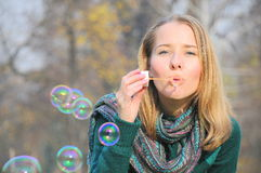Woman blowing bubbles. Portrait of a beautiful girl blowing soap bubbles Stock Photos