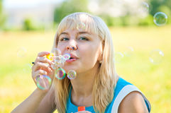 Woman blowing bubbles. In park Royalty Free Stock Photo