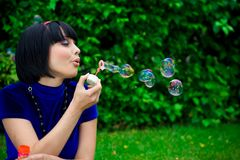 Woman blowing bubbles Royalty Free Stock Image