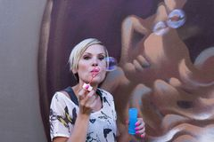 Woman is blowing bubbles Stock Image