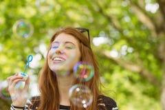 Woman blowing bubbles at park Stock Photos