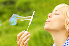 Woman blowing bubbles Stock Images