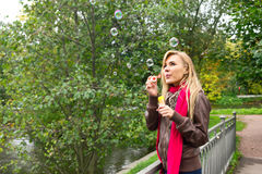 Woman blowing bubbles Stock Photography