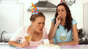 Woman blowing candle while celebrating her birthday with a friend