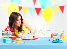 Woman blowing candles of the cake Stock Photo