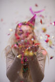 Woman blowing confetti in the air Royalty Free Stock Image