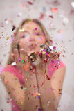 Woman blowing confetti in the air Royalty Free Stock Images
