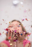 Woman blowing confetti in the air Royalty Free Stock Photo