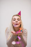Woman blowing confetti in the air. Beautiful young woman celebrating new year and chrismas party while blowing confetti decorations to camera Stock Image