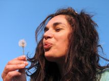 Woman blowing dandelion Royalty Free Stock Images