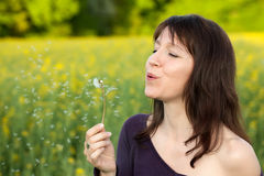 Woman blowing dandelion Stock Image
