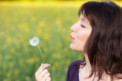 Woman blowing dandelion Stock Photo