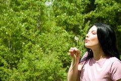 Woman blowing dandelion royalty free stock photo