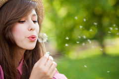 Woman blowing dandelion Royalty Free Stock Photos