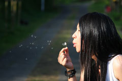 Woman blowing a dandelion. In the wind Stock Photography