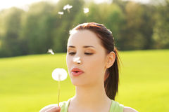 Woman blowing on a dandelion Stock Image