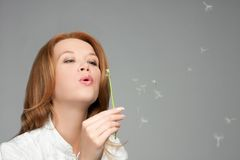 Woman blowing at dandelion Royalty Free Stock Image