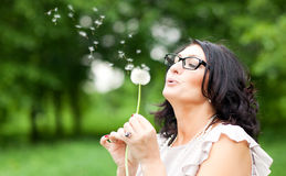 Woman blowing on a dandelion Royalty Free Stock Image
