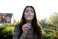 Woman blowing on dandelion in the garden Royalty Free Stock Photography