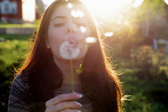 Woman blowing on dandelion in the garden Royalty Free Stock Image