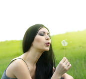 Woman blowing dandelion on the meadow Royalty Free Stock Photography