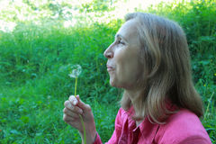 Woman blowing on a dandelion Royalty Free Stock Photography