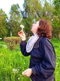 Woman blowing dandelion Stock Photos