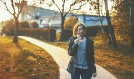 Woman blowing dandelion on path