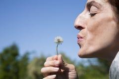 Woman blowing dandelion plant Stock Photo