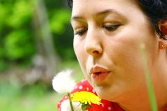 Woman blowing dandelion seeds Stock Photos