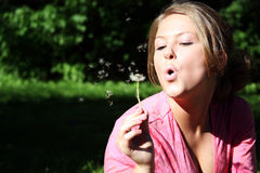 Woman blowing on the dandelion Stock Photo
