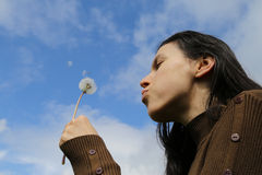Woman blowing dandelion Royalty Free Stock Photography