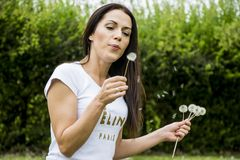 Woman blowing dandelion Stock Images