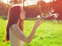 Woman blowing on a dandelion. Young woman blowing on a white dandelion stock image