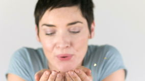 Woman blowing golden sparkles out of her hands in Slow motion Royalty Free Stock Photography