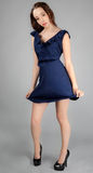 Woman With Blowing Hair and Dress. An image of an attractive young woman in blue mini dress with wind blowing Stock Photography