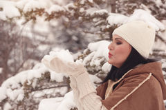 Woman blowing handful of snow Royalty Free Stock Photos
