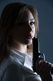 Woman blowing at her guns barrel Stock Photography