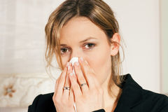 Woman blowing her nose. Woman with a flu or an allergy blowing her nose into her handkerchief Royalty Free Stock Images