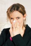 Woman blowing her nose. Woman with a flu or an allergy blowing her nose into her handkerchief Royalty Free Stock Photography