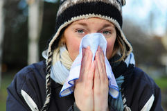 Woman blowing her nose. Into tissue, winter outdoor portrait Stock Image