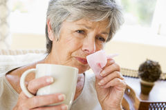 Woman Blowing Her Nose. A vWoman Blowing Her Nose Royalty Free Stock Photography