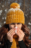 Woman blowing her nose into tissue, winter outdoor portrait Stock Image