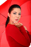 Woman Blowing Kiss. Attractive young woman posing with umbrella blowing kiss stock photo