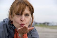 Woman blowing kiss. Portrait of middle aged auburn woman blowing kiss on beach stock photos