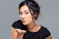 Woman blowing kiss at camera Royalty Free Stock Photography
