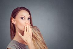 Woman blowing a kiss puckered lips covering mouth with hand royalty free stock images