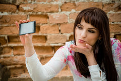 Woman blowing a kiss while taking selfie Stock Image