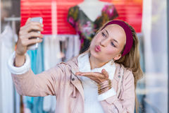 Woman blowing kiss and taking selfies Stock Photos